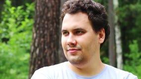 El hombre hermoso sonríe y presenta en parque del verano almacen de metraje de vídeo