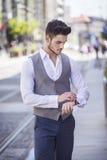 El hombre hermoso vistió elegante la mirada de su reloj Foto de archivo libre de regalías