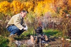 El hombre hierve la caldera fuliginosa en el fuego Imágenes de archivo libres de regalías