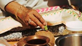 El hombre hindú pinta el cocounut con crema roja almacen de metraje de vídeo