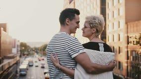 El hombre hispánico joven hermoso sube a la mujer caucásica, abraza y los besos en un puente de la puesta del sol de la tarde de  metrajes