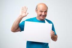 El hombre hispánico mayor con el bigote sostiene el blanco firma adentro un fondo del blanco del estudio fotografía de archivo