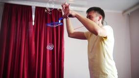 El hombre hizo un funcionamiento espectacular con las burbujas de jabón En una burbuja grande sopló las porciones de pequeñas bur metrajes