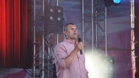El hombre hosco canta una canción en el micrófono durante un funcionamiento en etapa en un concierto de rock Hombre del primer Ru