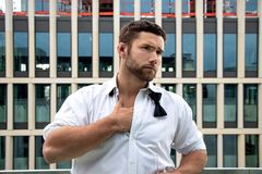 El hombre hunky hermoso en smoking, camisa desabrochada y lazo se coloca en el balcón del hotel, bebiendo una bebida foto de archivo