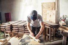 El hombre iguala una barra de madera con una fresadora fotos de archivo