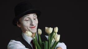 El hombre imita con un ramo de flores en un fondo negro almacen de metraje de vídeo