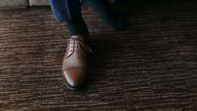El hombre implica cordones en los zapatos de cuero marrones almacen de metraje de vídeo