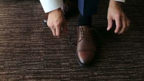 El hombre implica cordones en los zapatos de cuero marrones almacen de video