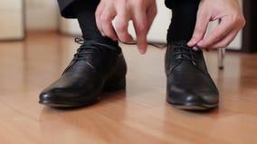 El hombre implica cordones en los zapatos de cuero negros almacen de metraje de vídeo