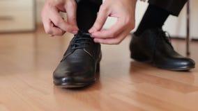 El hombre implica cordones en los zapatos de cuero negros almacen de video