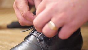 El hombre implica sus cordones en sus zapatos negros almacen de metraje de vídeo