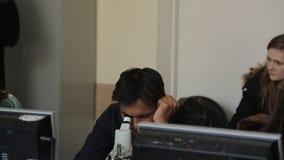 El hombre indio mira a través de un microscopio en la sala de clase para la biología almacen de video