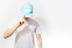 El hombre, individuo en el blanco en blanco, gorra de béisbol de la turquesa, en a Foto de archivo