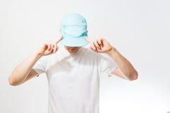 El hombre, individuo en el blanco en blanco, gorra de béisbol de la turquesa, en a Imagenes de archivo