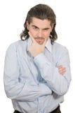 El hombre infeliz hermoso joven lleva a cabo su mano en la barbilla foto de archivo