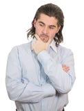 El hombre infeliz joven lleva a cabo la mano en la barbilla y piensa fotografía de archivo libre de regalías