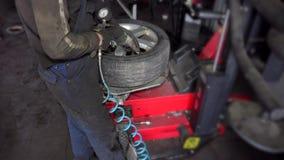 El hombre infla el aire del neumático en la máquina del montaje almacen de video