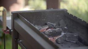 El hombre infla el fuego Carbones en un brasero El hombre para balancear una pala sobre los carbones El hombre hace una cena El h almacen de metraje de vídeo