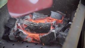 El hombre infla el fuego Carbones en un brasero El hombre para balancear una pala sobre los carbones El hombre hace una cena La p almacen de video