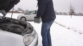 El hombre instala la batería en el coche en el invierno, el comienzo del problema el coche en el MES frío, lento almacen de video