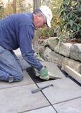 El hombre instala la losa en patio foto de archivo