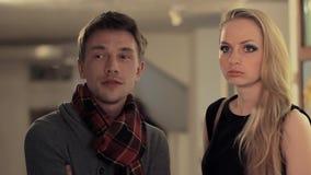 El hombre inteligente joven viene charla a la muchacha atractiva en galería de arte almacen de metraje de vídeo