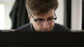 El hombre inteligente que lleva gafas trabaja en el ordenador en estudio almacen de metraje de vídeo