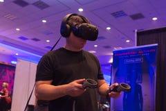 El hombre intenta controles de las auriculares y de la mano de HTC Vive de la realidad virtual Fotografía de archivo libre de regalías