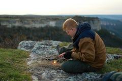 El hombre intenta hacer un fuego con un pedernal imagen de archivo libre de regalías