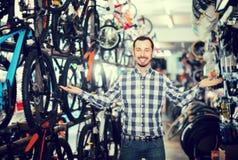 El hombre interesado en tienda de la bicicleta elige para sí mismo la bici de los deportes Fotografía de archivo