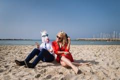El hombre inusual joven en máscara divertida está hablando con la novia Imágenes de archivo libres de regalías