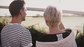 El hombre irreconocible y la mujer de la cámara lenta se colocan cerca del acuario grande con agua y la mala hierba del mar Pares almacen de metraje de vídeo