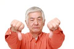El hombre japonés mayor con los pulgares abajo gesticula Fotografía de archivo