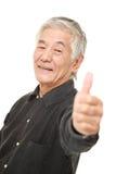 El hombre japonés mayor con los pulgares sube gesto Foto de archivo