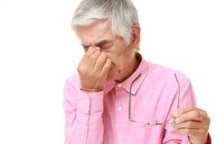 El hombre japonés mayor sufre de Asthenopia Imágenes de archivo libres de regalías