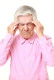 El hombre japonés mayor sufre de dolor de cabeza Imagen de archivo