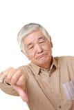 El hombre japonés mayor con los pulgares abajo gesticula Foto de archivo libre de regalías
