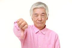 El hombre japonés mayor con los pulgares abajo gesticula Imagen de archivo libre de regalías