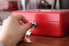El hombre joven abre la caja de dinero de la seguridad que mueve la llave fotos de archivo libres de regalías