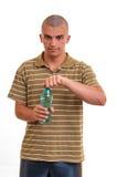 El hombre joven abre una botella de agua Imagen de archivo libre de regalías
