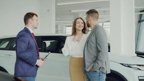 El hombre joven acertado está comprando el coche para su esposa que sacude las manos con el agente de la representación entonces  metrajes