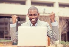 El hombre joven acertado feliz del retrato con el ordenador portátil celebra éxito Fotografía de archivo libre de regalías
