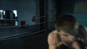 El hombre joven activo perfora rápidamente la cámara en el ring de boxeo en gimnasio industrial almacen de metraje de vídeo