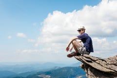 El hombre joven admira el paisaje de la montaña fotografía de archivo