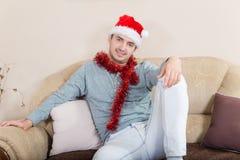 El hombre joven adornado con las decoraciones de la Navidad y el sombrero rojo Foto de archivo libre de regalías