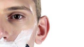 El hombre joven afeita la mejilla usando las hojas de afeitar Fondo blanco Primer metrajes