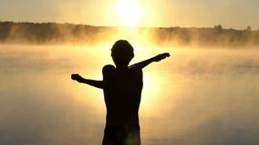 El hombre joven agita sus brazos en un banco del lago en la puesta del sol almacen de metraje de vídeo