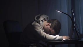 El hombre joven agotado despierta delante del ordenador en la noche metrajes