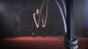 El hombre joven apto lleva a cabo la cuerda en sus manos y hace entrenamiento pesado del entrenamiento de la cuerda metrajes